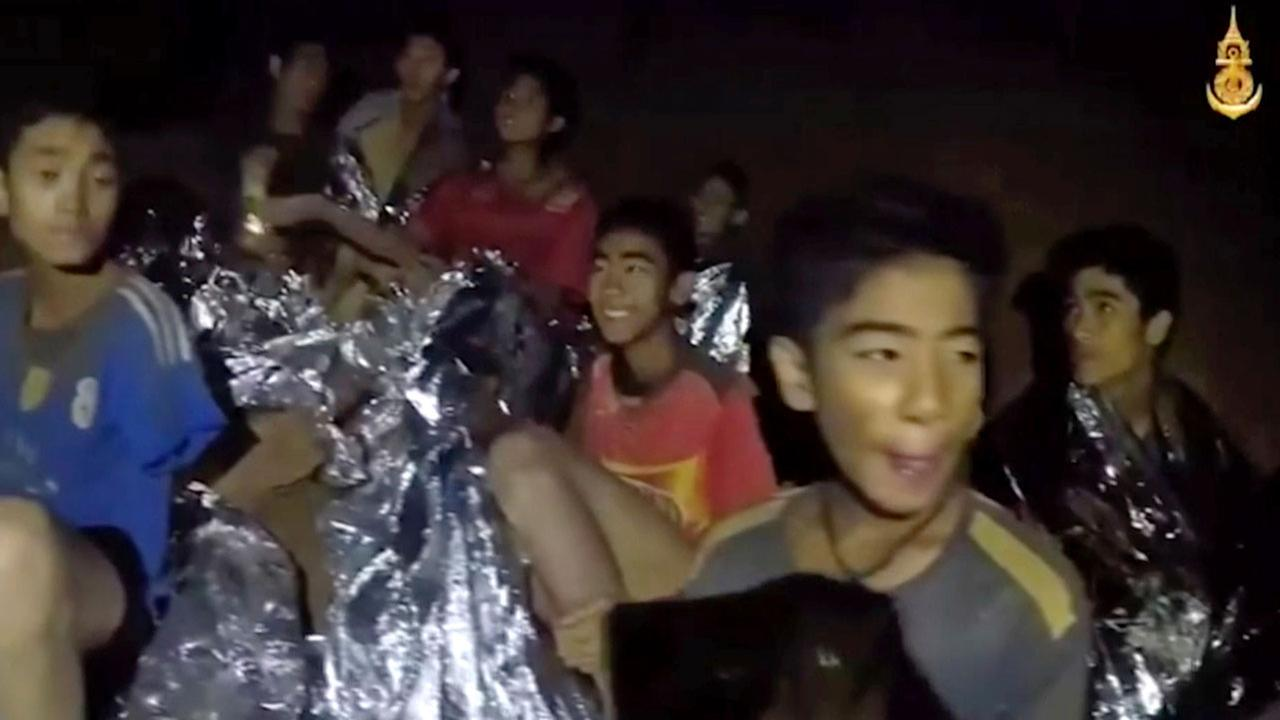 In this July 3 image, Thai boy smiles as Thai Navy SEAL medic help injured children inside a cave in Mae Sai, northern Thailand.