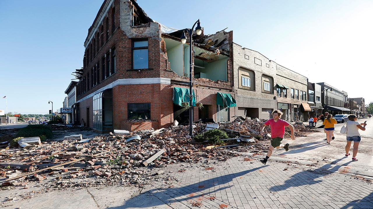 A local resident runs past a tornado-damaged building on Main Street, Thursday, July 19, 2018, in Marshalltown, Iowa.  (AP Photo/Charlie Neibergall)