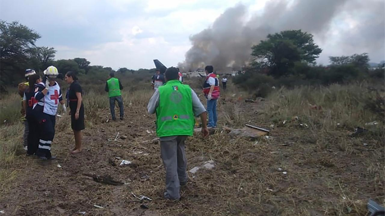 Rescue workers and firefighters at the site where an Aeromexico airliner crashed in a field near the airport of Durango, Mexico.  (Civil Defense Office of Durango Photo via AP)