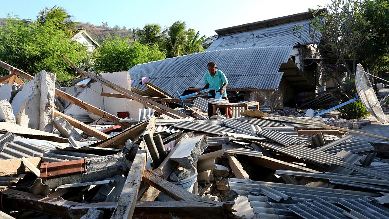 Usable items are salvaged from a home destroyed in an earthquake in North Lombok, Indonesia, Monday, Aug. 6, 2018.