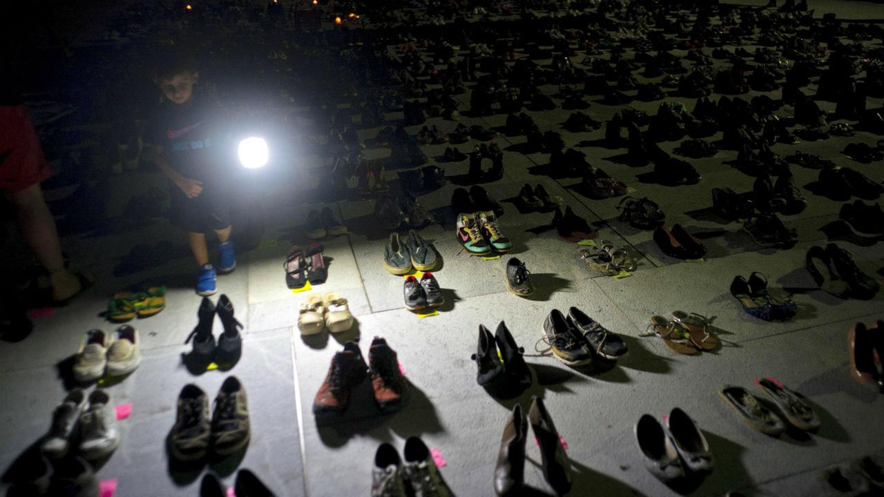 A child illuminates hundreds of shoes at a memorial for those killed by Hurricane Maria, in front of the Puerto Rico Capitol, in San Juan, Friday, June 1, 2018.