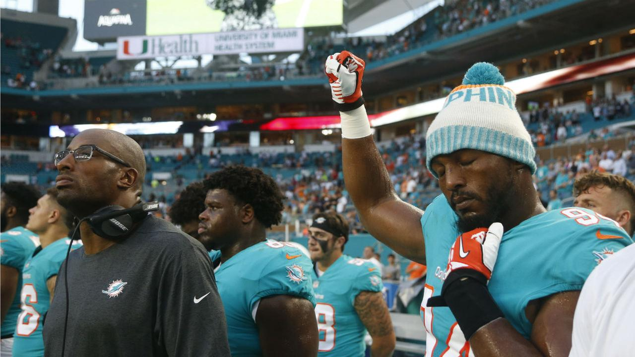 Miami Dolphins defensive end Robert Quinn raises his right fist during the singing of the national anthem, before the teams football game against the Tampa Bay Buccaneers.
