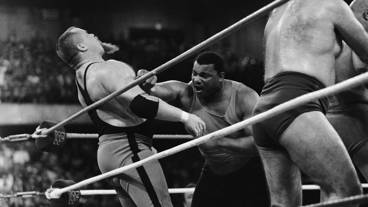 William Perry, right, lands a punch on pro wrestler Jim The Anvil Neidhart during the Over-The-Top-Rope battle royal at Wrestlemania 2 on April 7, 1986.