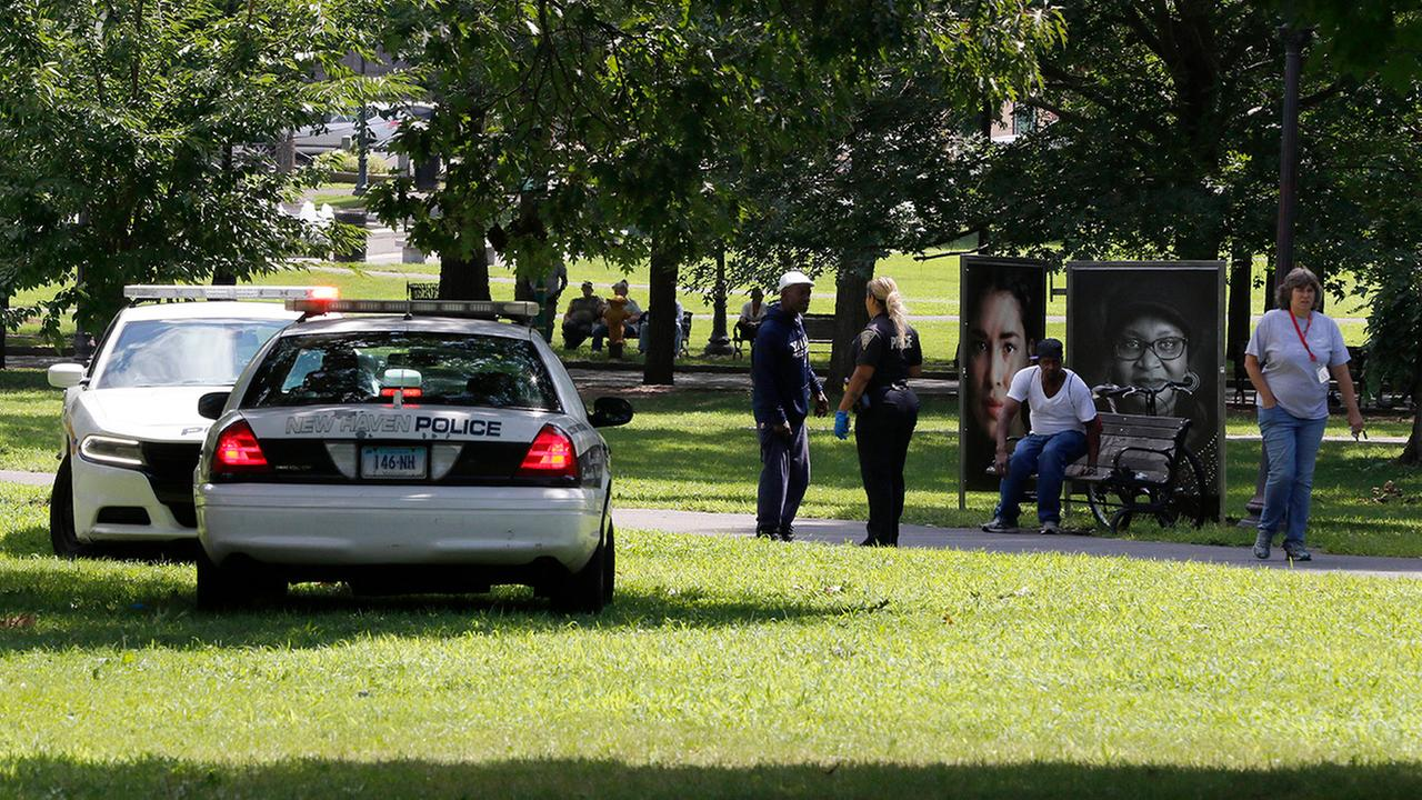 A police officer speaks to a man walking on New Haven Green, Wednesday, Aug. 15, 2018, in New Haven, Conn.