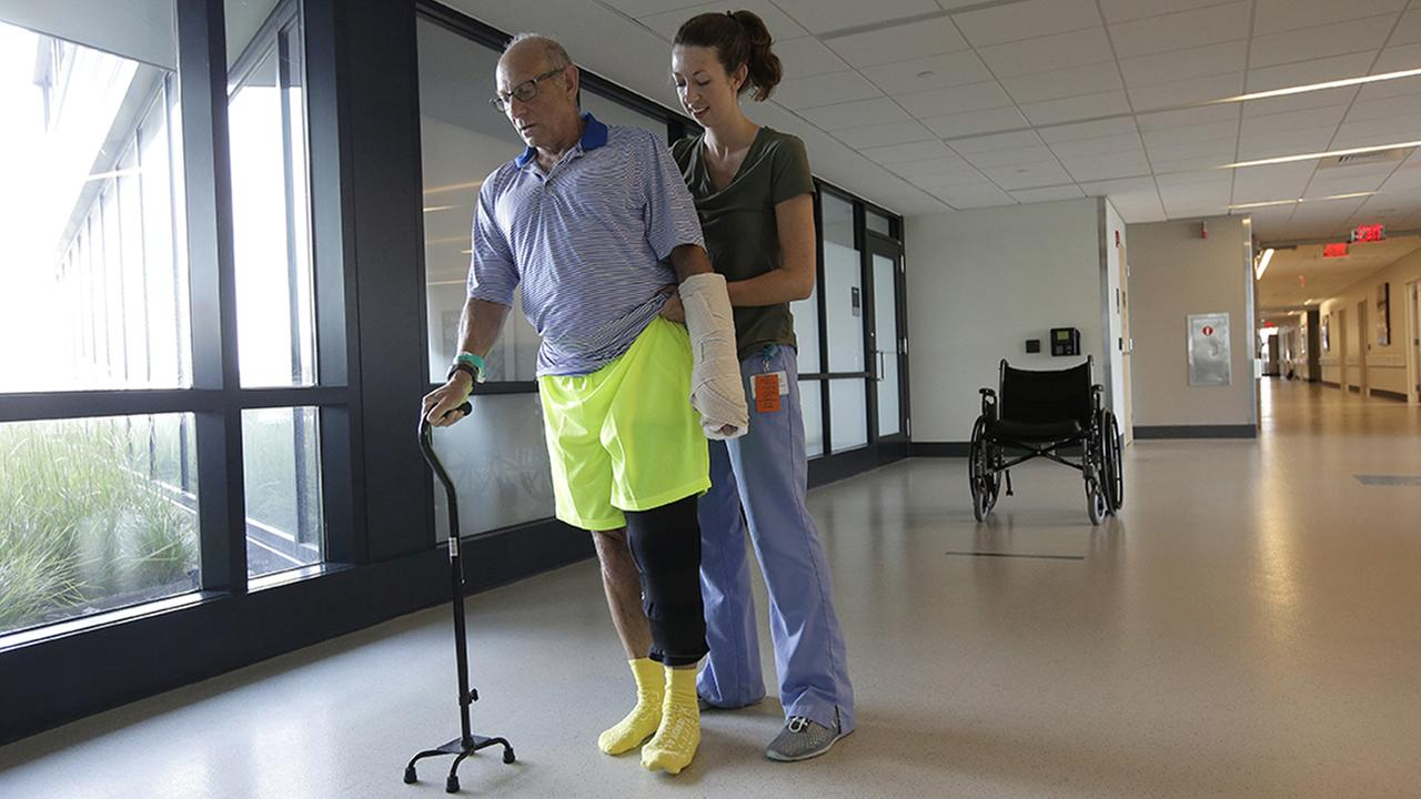 William Lytton, of Scarsdale, N.Y., left, is assisted by physical therapist Caitlin Geary at Spaulding Rehabilitation Hospital, in Boston, while recovering from a shark attack.