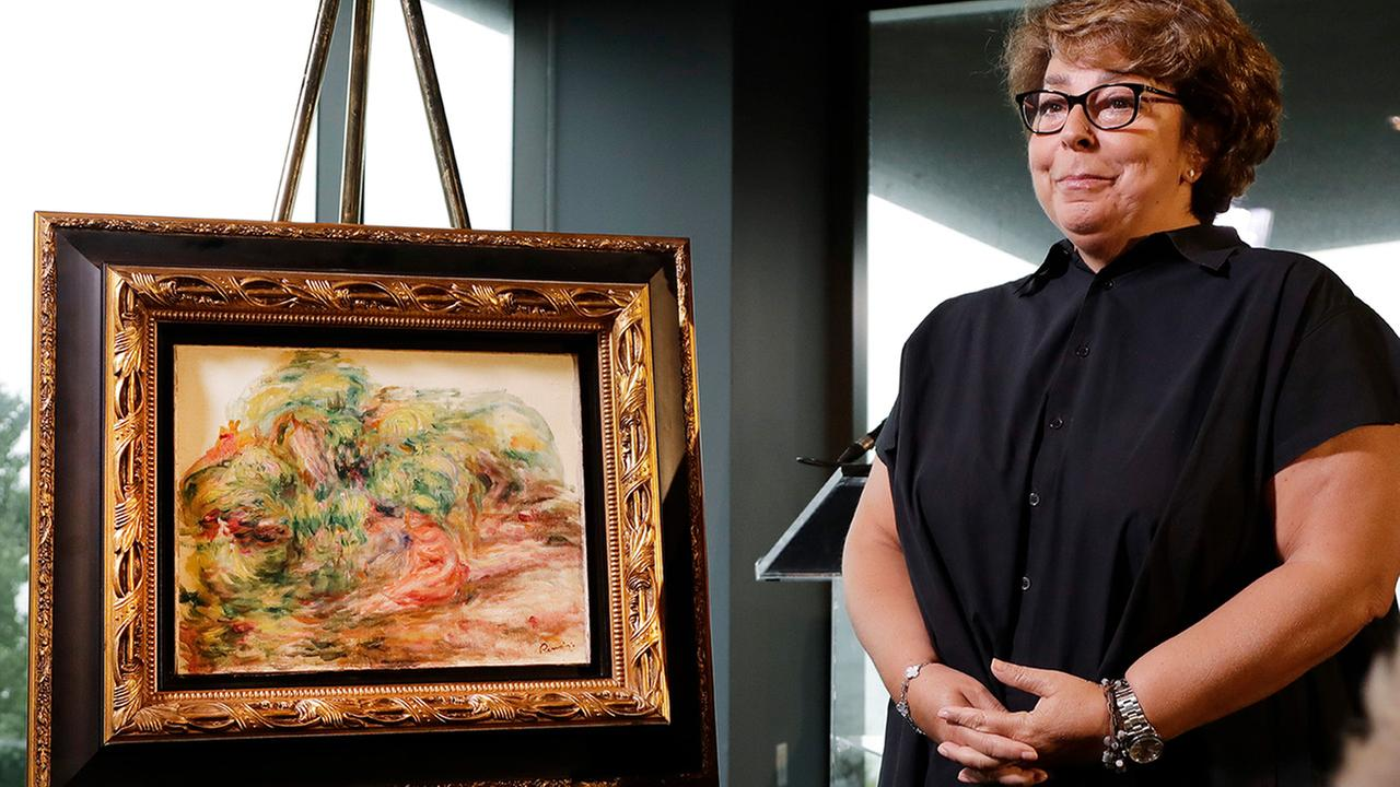 Sylvie Sulitzer stands with a Renoir painting that was returned to her in a reparation ceremony at a news conference, Wednesday, Sept. 12, 2018, in New York.