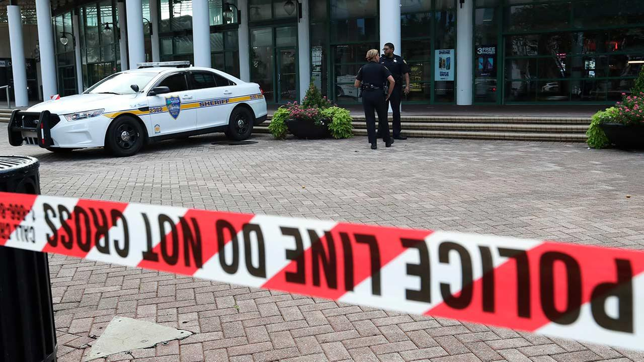 Jacksonville police officers guard an area Monday, Aug. 27, 2018, near the scene of a fatal shooting at The Jacksonville Landing in Jacksonville, Fla. (AP Photo/John Raoux)