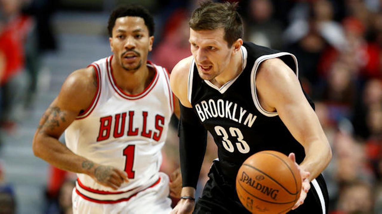 Brooklyn Nets forward Mirza Teletovic (33) advances past Chicago Bulls guard Derrick Rose (1) during the first half of an NBA basketball game on Tuesday, Dec. 30, 2014, in Chicago.