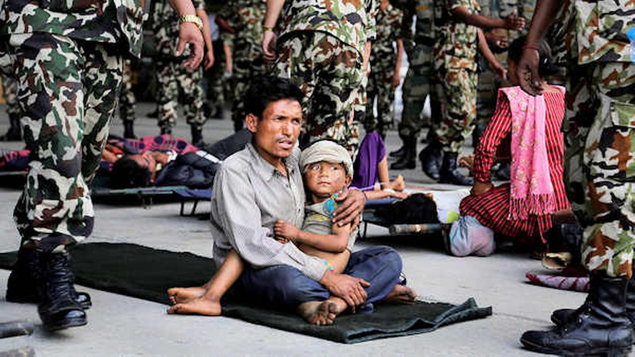 A man sits with a child on his lap as victims of Saturdays earthquake, wait for ambulances after being evacuated at the airport in Kathmandu, Nepal, Monday, April 27, 2015.