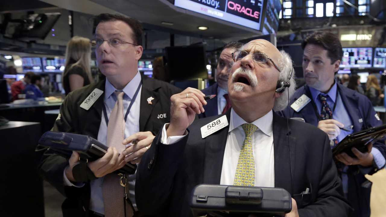 Peter Tuchman, foreground right, works with fellow traders on the floor of the New York Stock Exchange, Monday, Aug. 24, 2015.