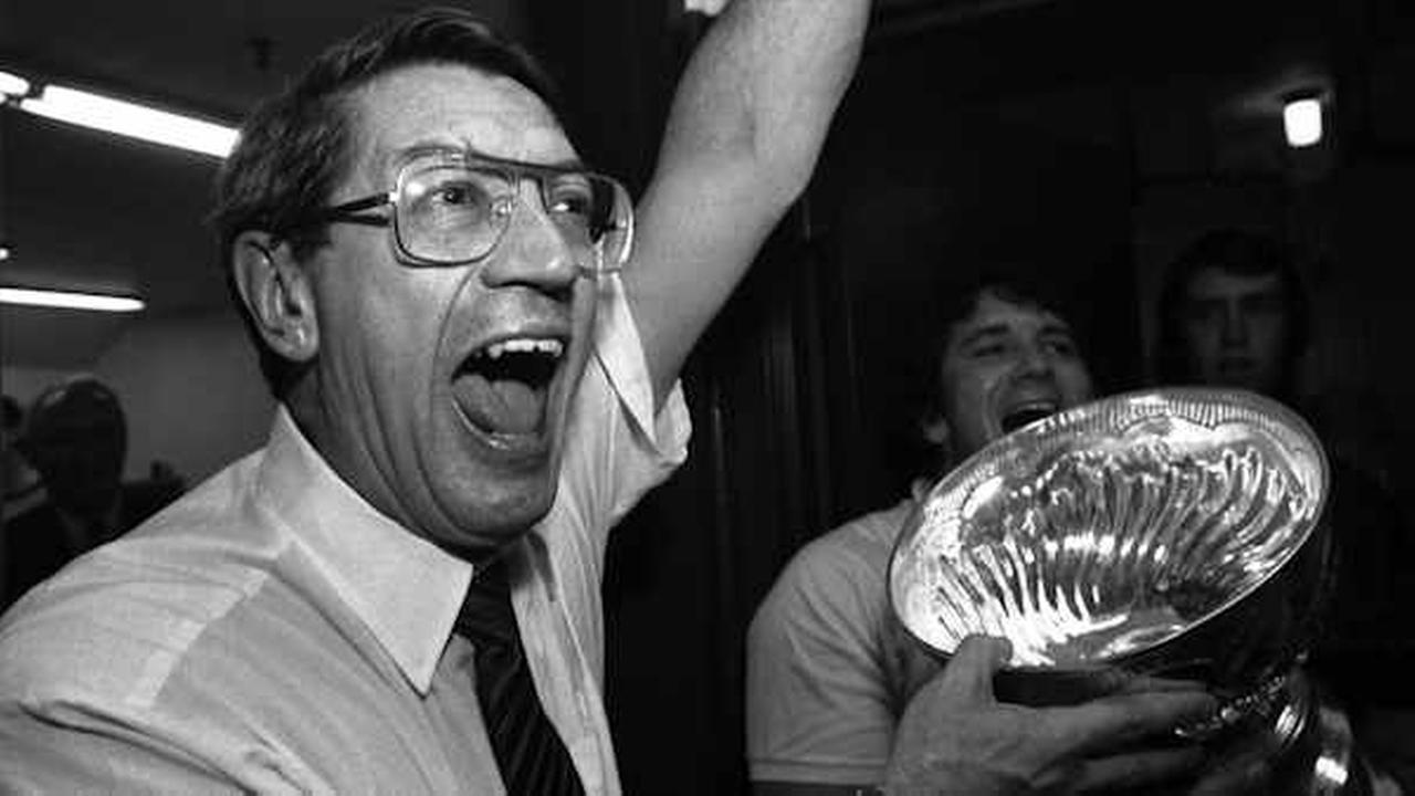 New York Islanders coach Al Arbour celebrates in the locker room as he drinks from the Stanley Cup after the Islanders won their fourth cup in a row