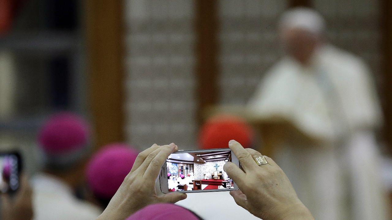 A Bishop takes a picture with a smartphone during a meeting with Pope Francis at the Shrine of Haemi, in South Korea, Sunday, Aug. 17, 2014.