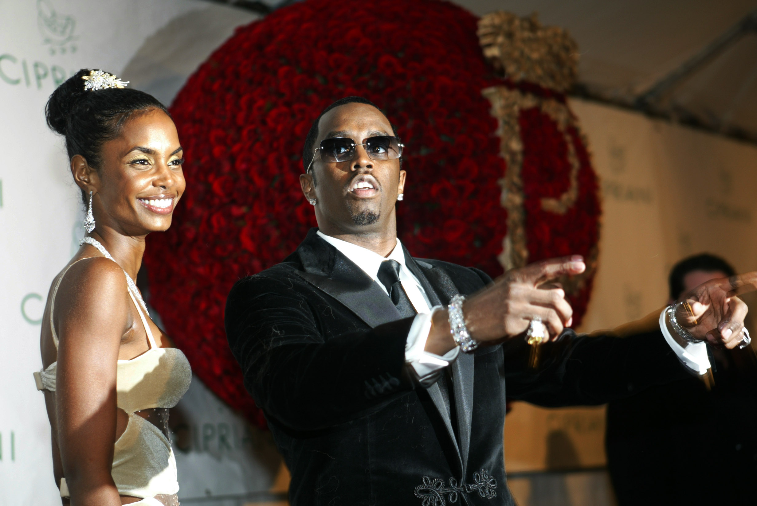 Sean P. Diddy Combs directs photographers as they sing Happy Birthday, to him as his date Kim Porter, left, listens, Thursday, Nov. 4, 2004.