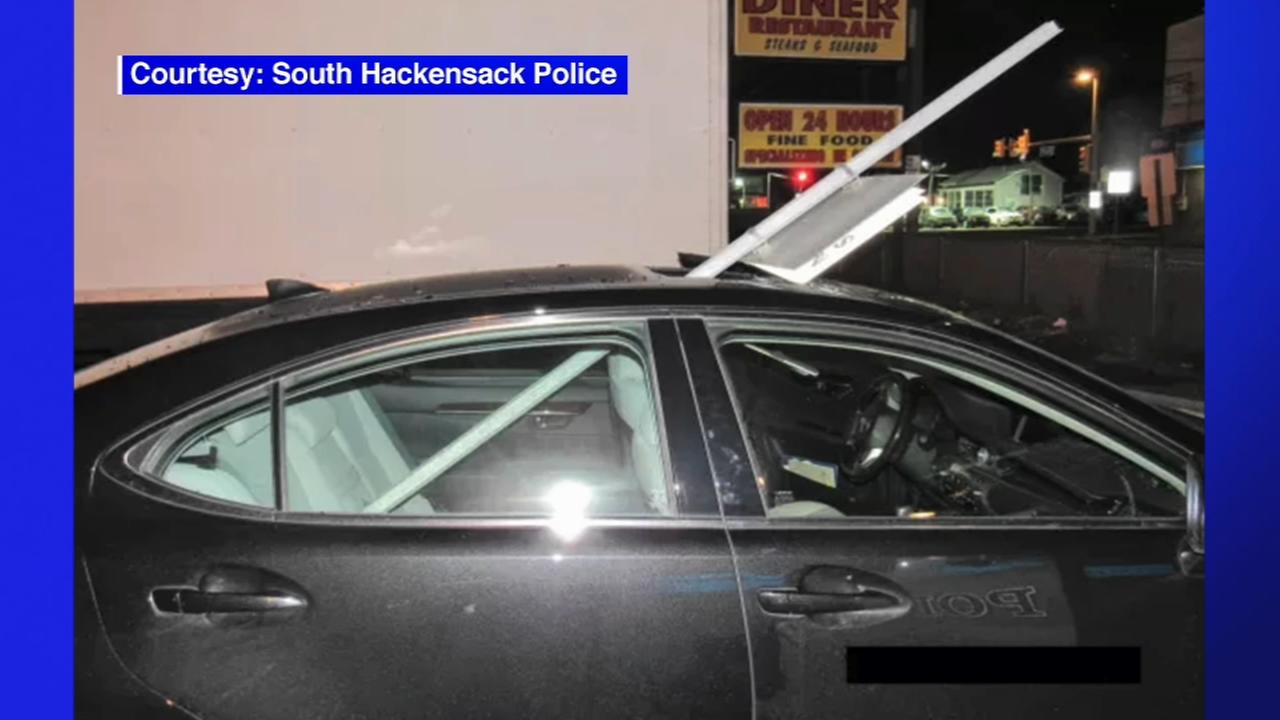 Woman arrested after driving with NJT sign through roof of car