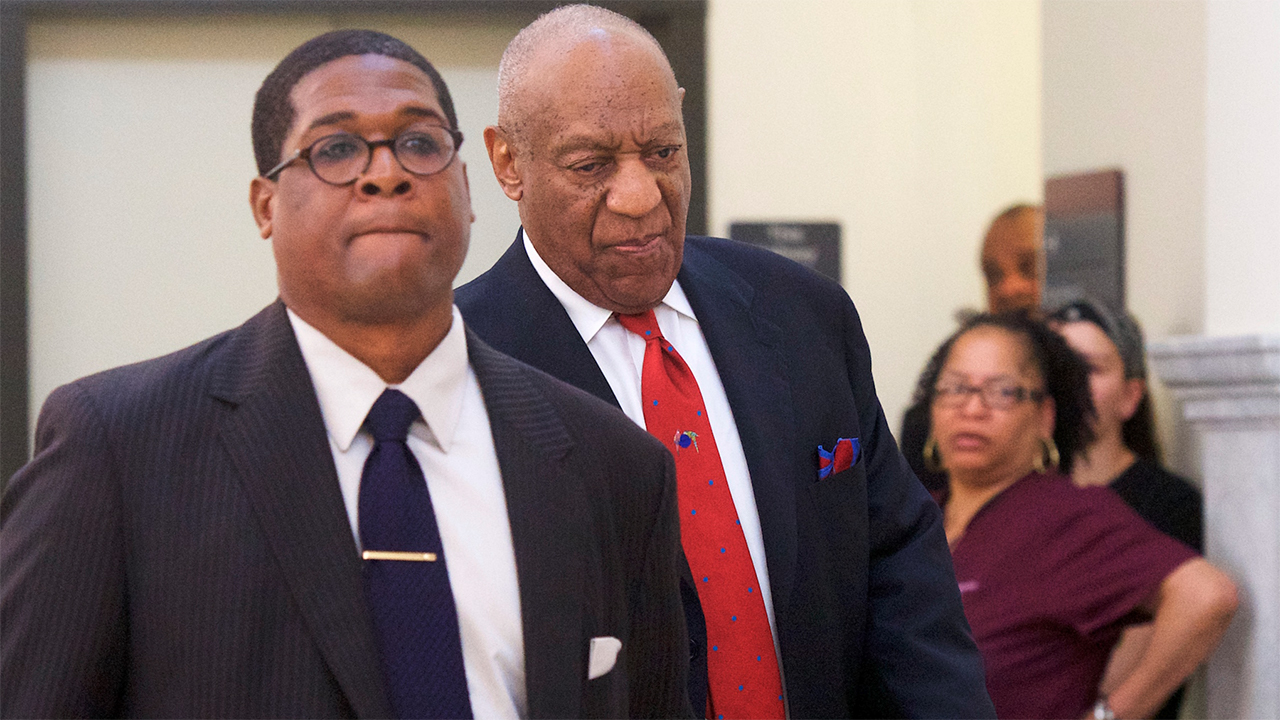 Bill Cosby walks through the Montgomery County Courthouse with his publicist, Andrew Wyatt, after being found guilty on all counts in his sexual assault retrial.