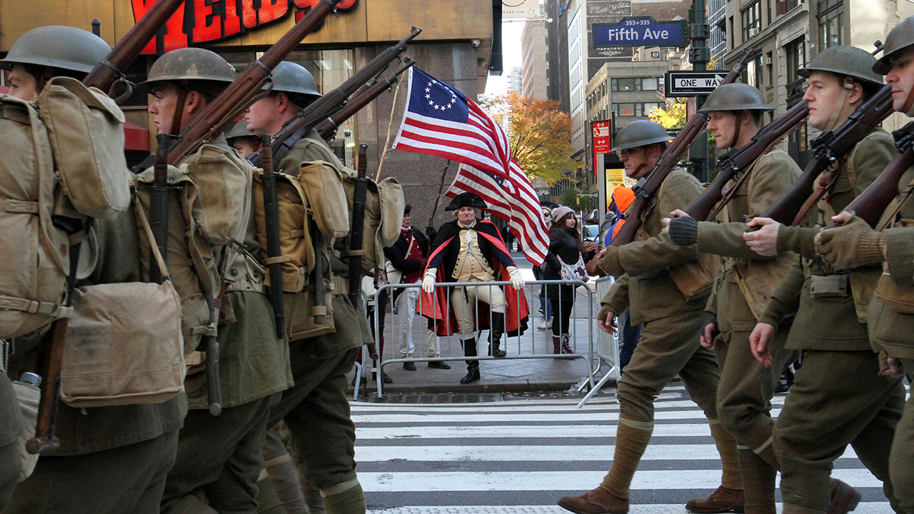 Dressed as General George Washington, Michael Drillo, of Scarsdale, New York, center, watches as the Veterans Day Parade makes its way up New Yorks Fifth Avenue.