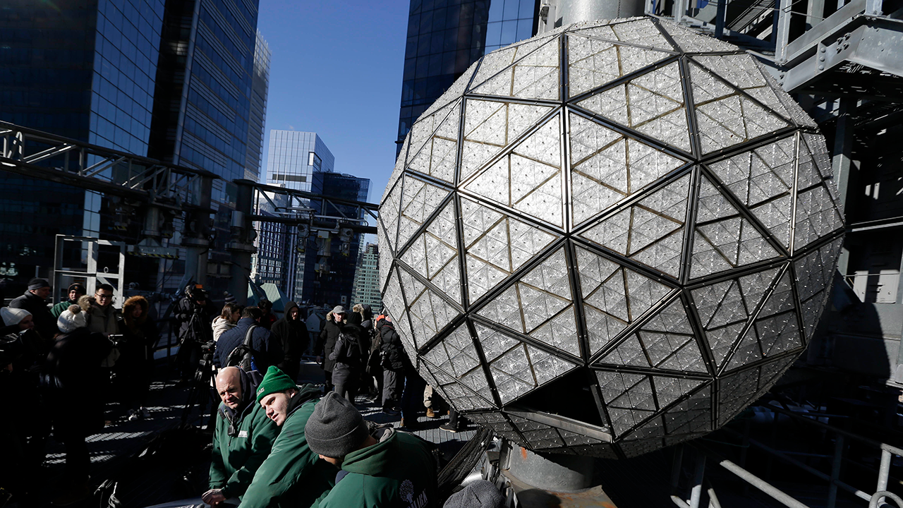 Workers prepare to install the last panels on the New Years Eve ball above Times Square, New York, Wednesday, Dec. 27, 2017.