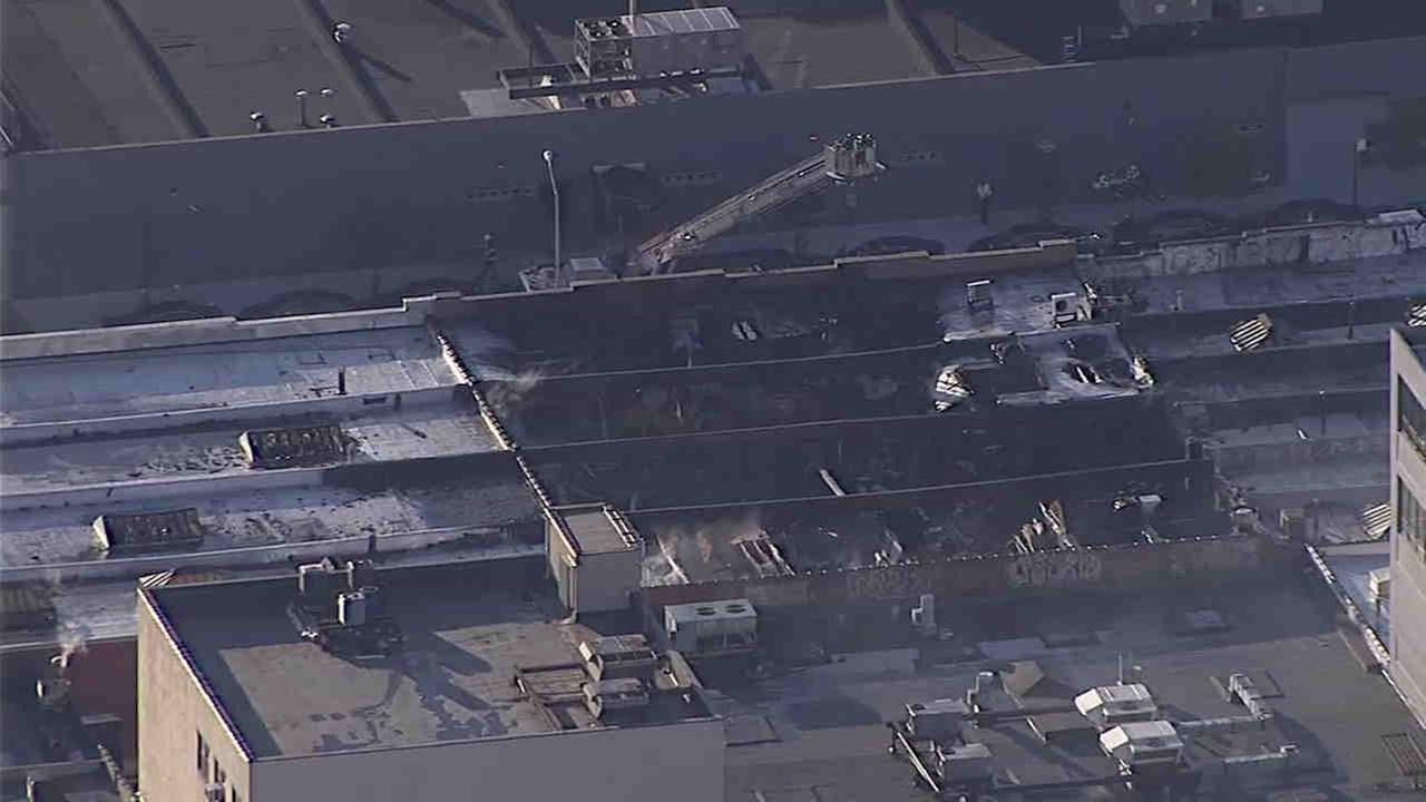A five-alarm fire continued to burn Thursday through a woodworking shop in the Sunnyside section of Queens.