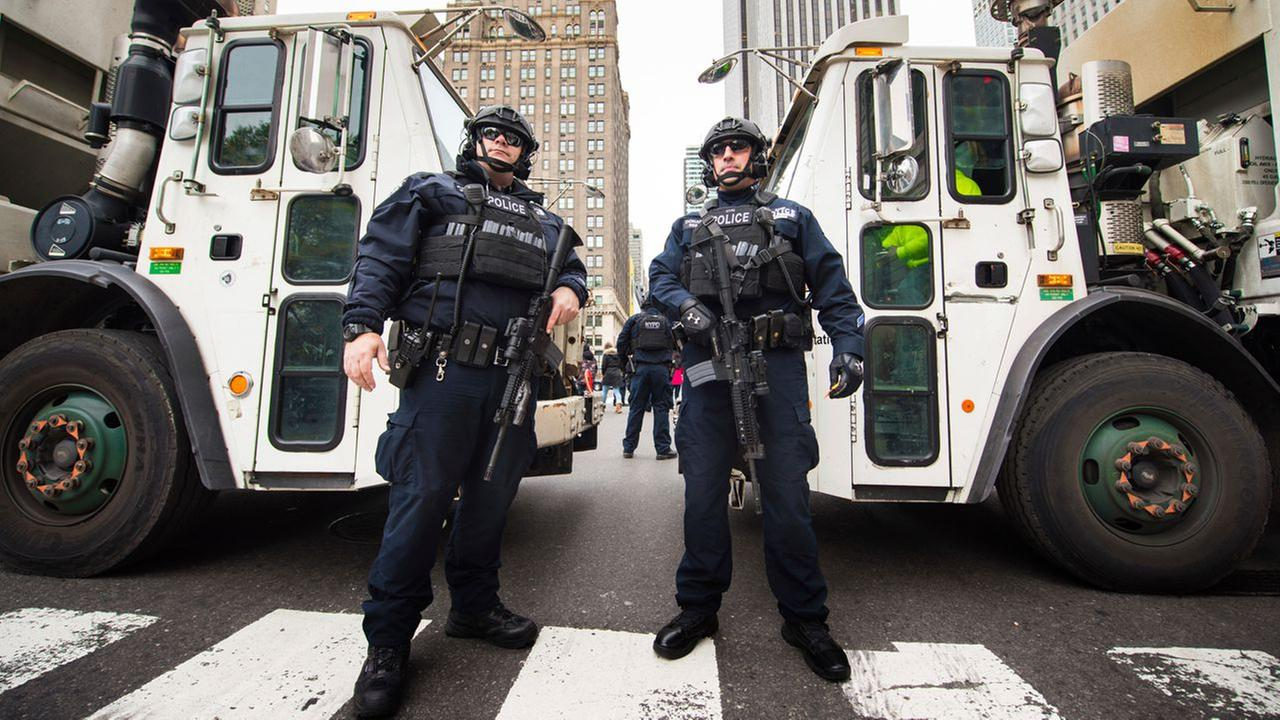 NYPD police officers stand guard in front of garbage trucks on 59th Street during the Macys Thanksgiving Day Parade on Thursday, Nov. 24, 2016, in New York.