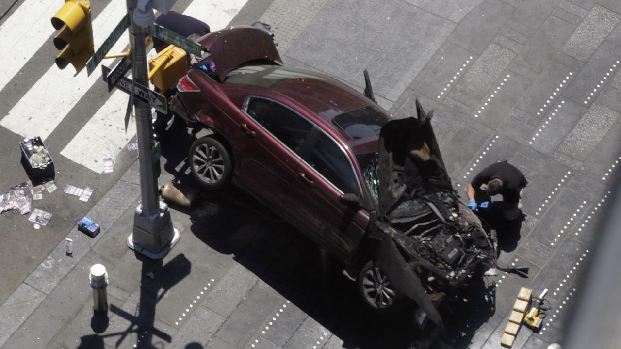 A police officer inspects a car crash, Thursday, May 18, 2017, in New Yorks Times Square.