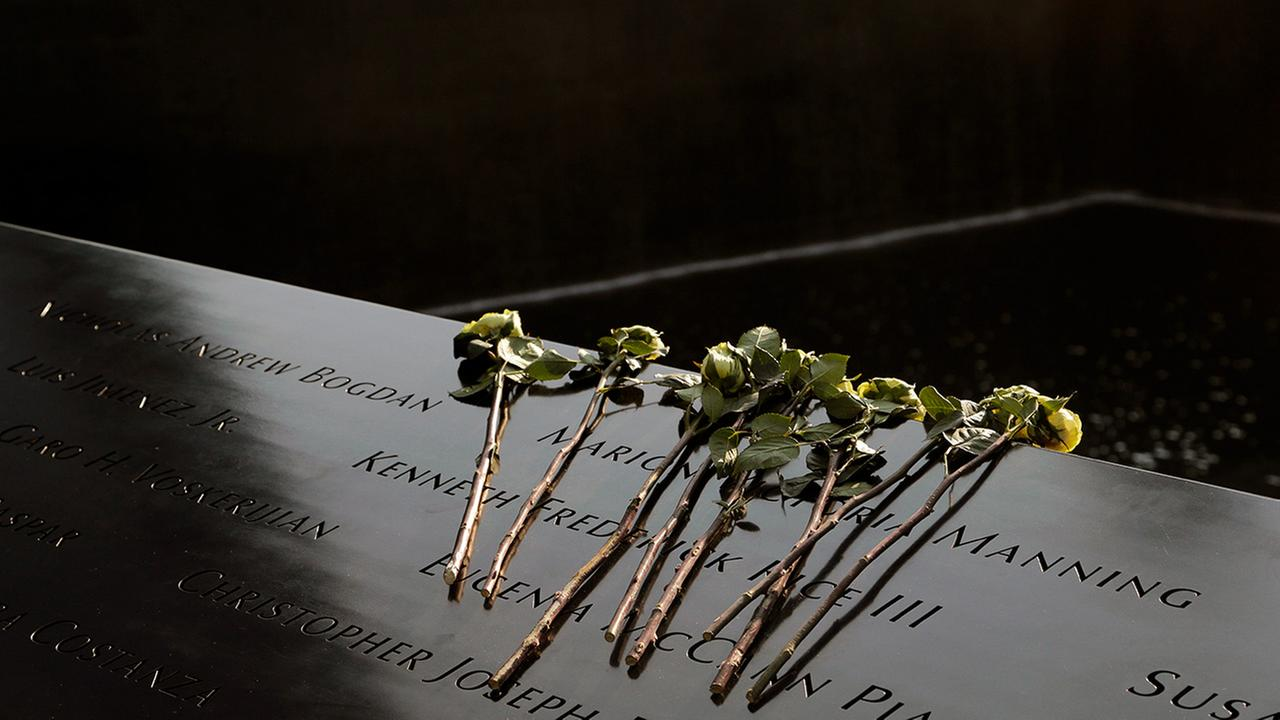 Flowers lay over the names of the victims of the 9/11 terrorist attacks before a ceremony at ground zero in New York, Monday, Sept. 11, 2017.