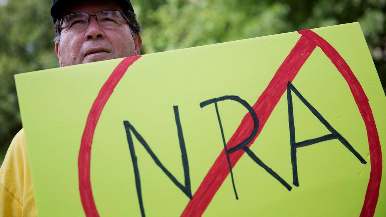 U.S. Army veteran Pax Riddle holds a sign during a rally protesting the National Rifle Associations annual convention a few blocks away in Atlanta, Saturday, April 29, 2017.