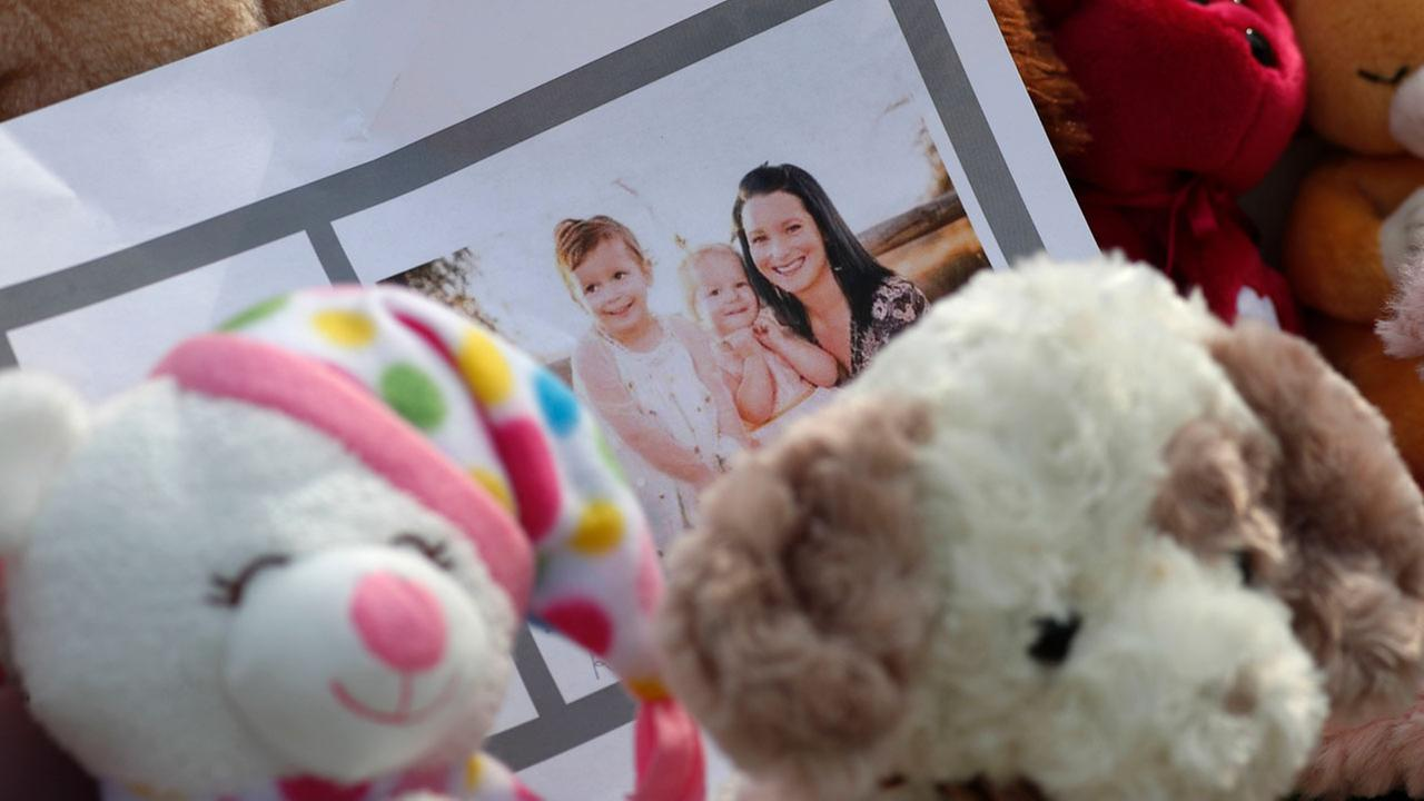 A photograph sits amid the tributes as they grow outside the home where a pregnant woman, Shanann Watts, and her two daughters, Bella and Celeste, lived Thursday, Aug. 16, 2018.