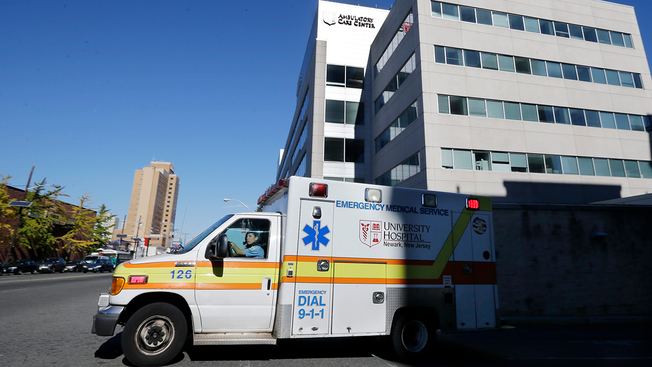 In this Oct. 27, 2014, file photo, an ambulance drives near University Hospital of Newark in Newark, N.J.