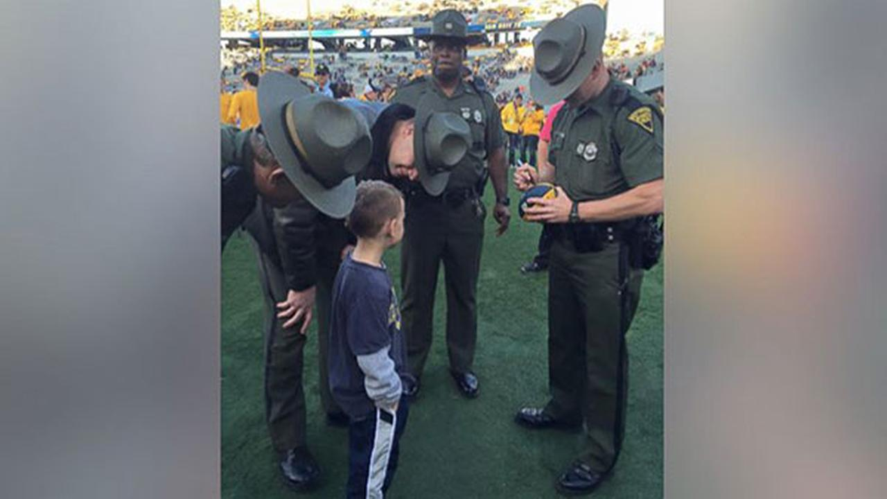 Boy asks for state troopers' autographs after football game