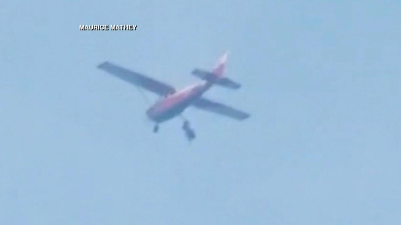 Skydiver stuck hanging from plane safely lands