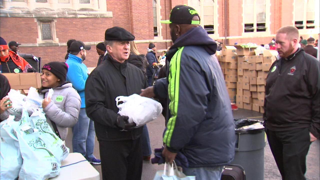 Archbishop Blase Cupich helped out at the Thanksgiving food pantry distribution at St. Columbanus Parish on East 77th Street.