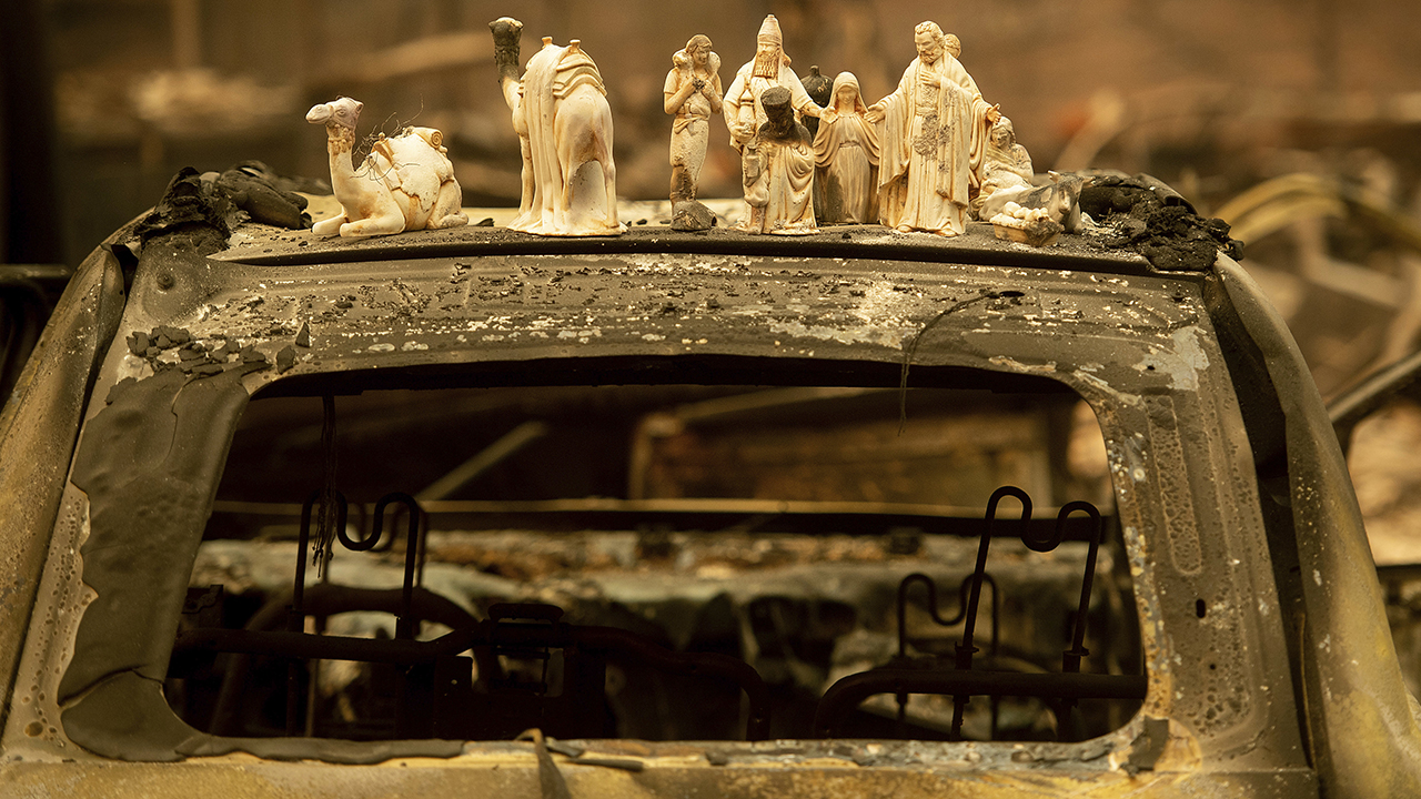 Following the Camp Fire, figurines rest atop a scorched car on Pearson Road, Monday, Nov. 12, 2018, in Paradise, Calif.