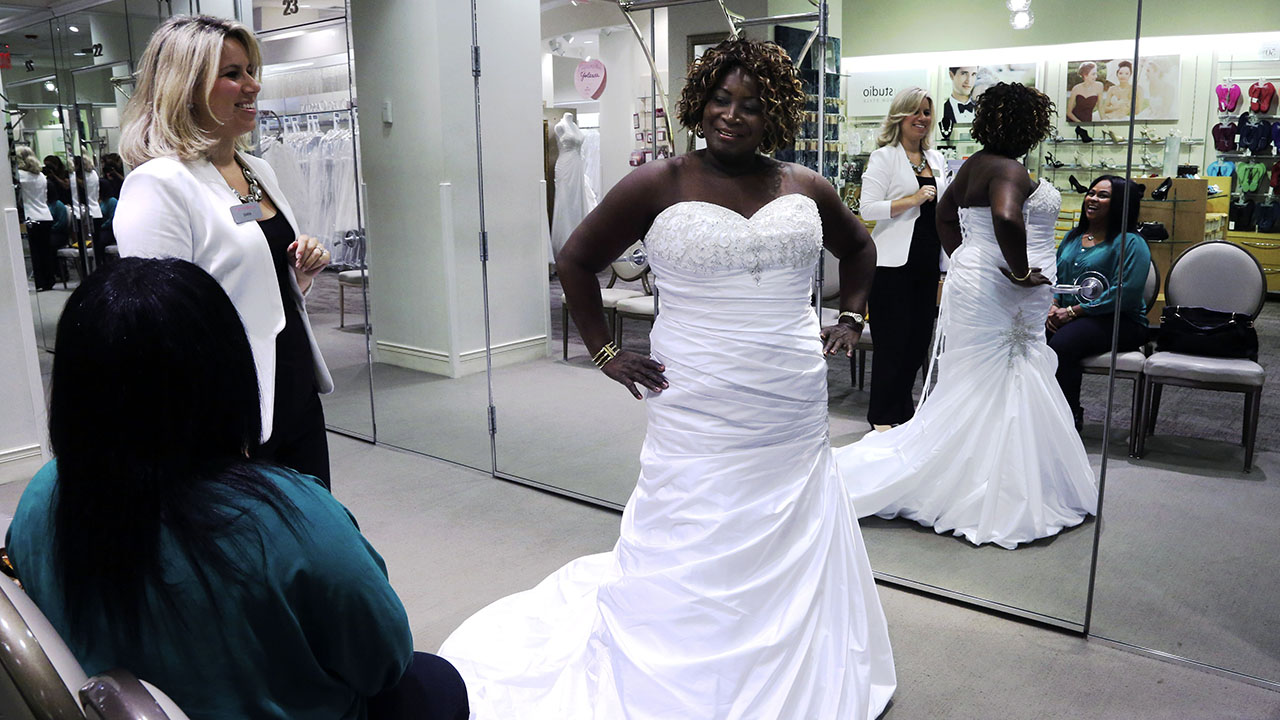 In this 2013 photo, Sara Musillo, left, assistant store manager at Davids Bridal in New York, assists Yolanda Royal, center, as she tries on wedding dresses with her niece.