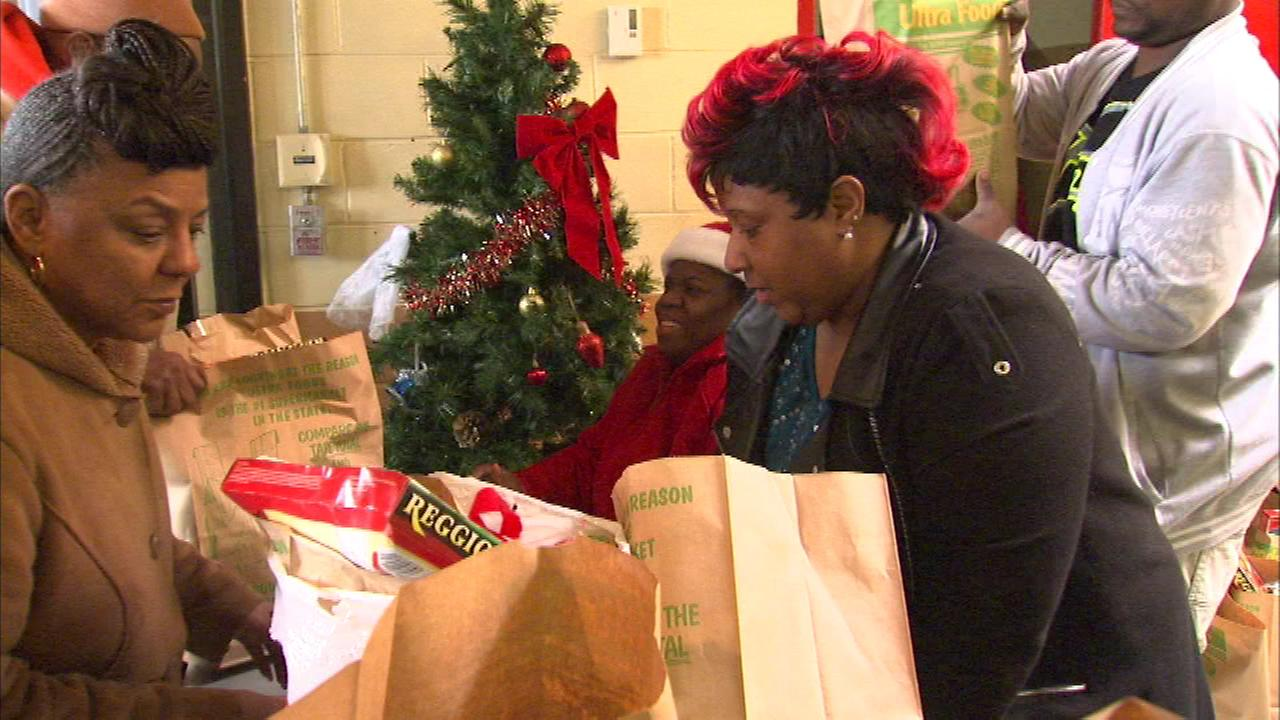 Volunteers at the Paul Hall Community Service Center pass out bags of groceries to people in need.