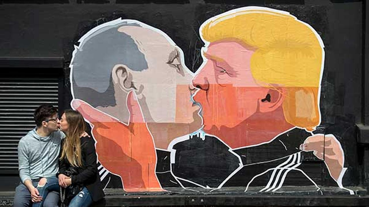 A couple kisses in front of graffiti depicting Vladimir Putin, left, and Donald Trump, on the walls of a bar in the old town in Vilnius, Lithuania, Saturday, May 14, 2016.