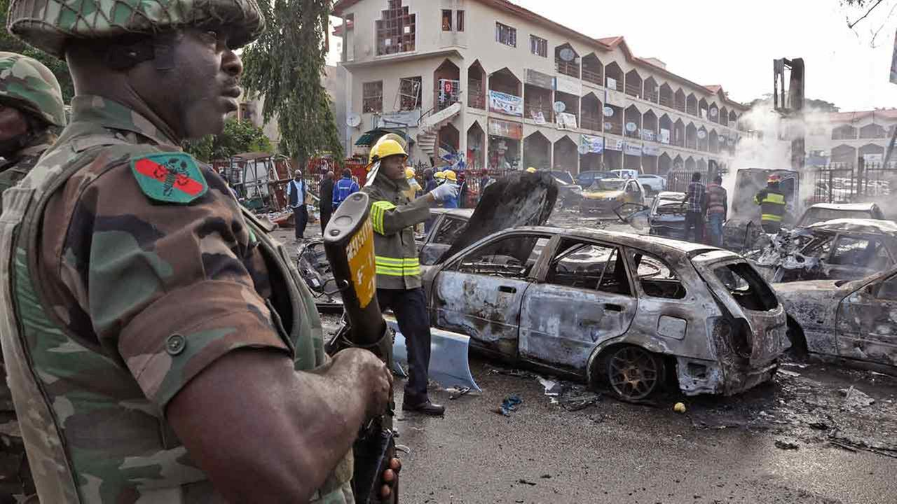 A Nigerian soldier stands guard at the scene of an explosion in Abuja, Nigeria, Wednesday, June 25, 2014. An explosion rocked a shopping mall in Nigerias capital Wednesday.