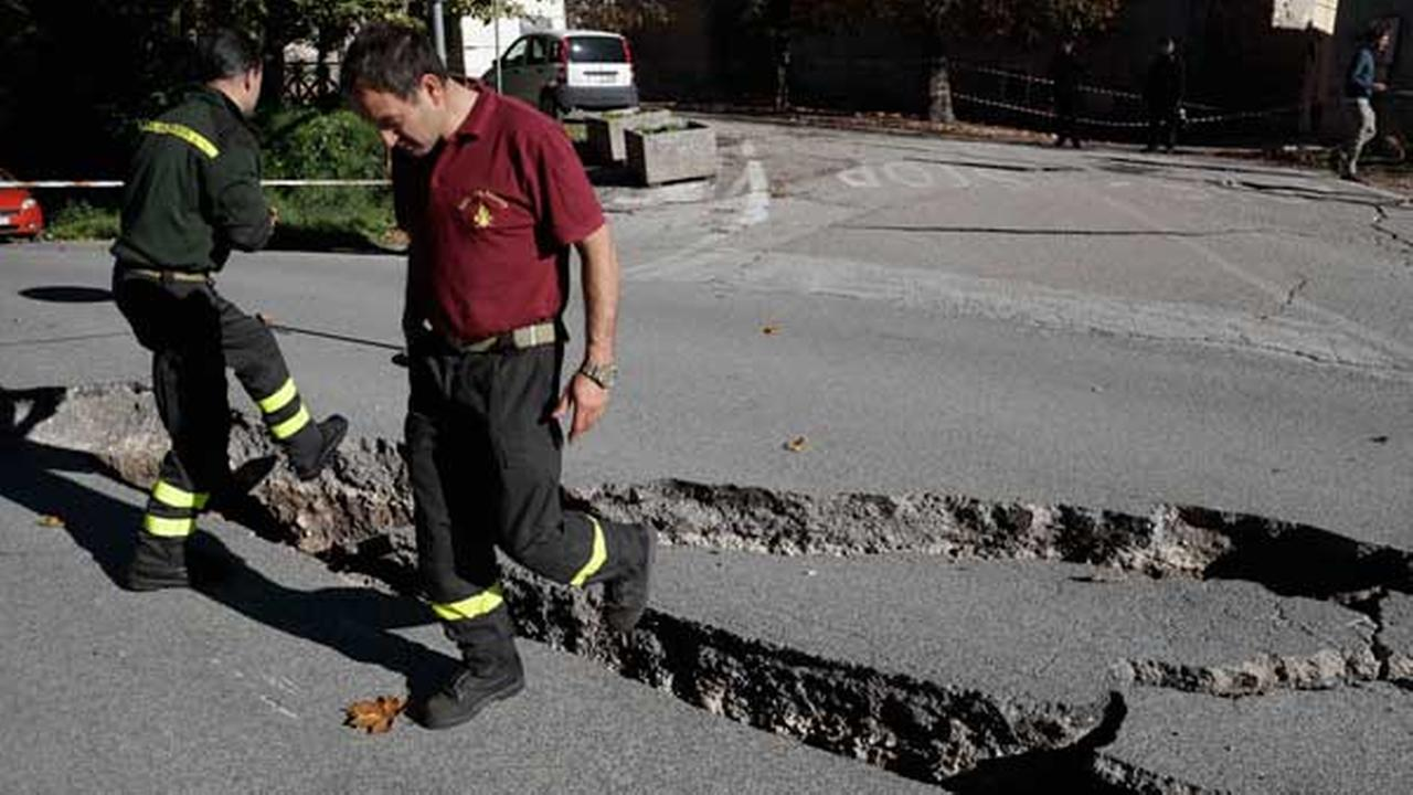 Firefighters inspect cracks in a road in Norcia, central Italy, after an earthquake with a preliminary magnitude of 6.6 struck central Italy, Sunday, Oct. 30, 2016.