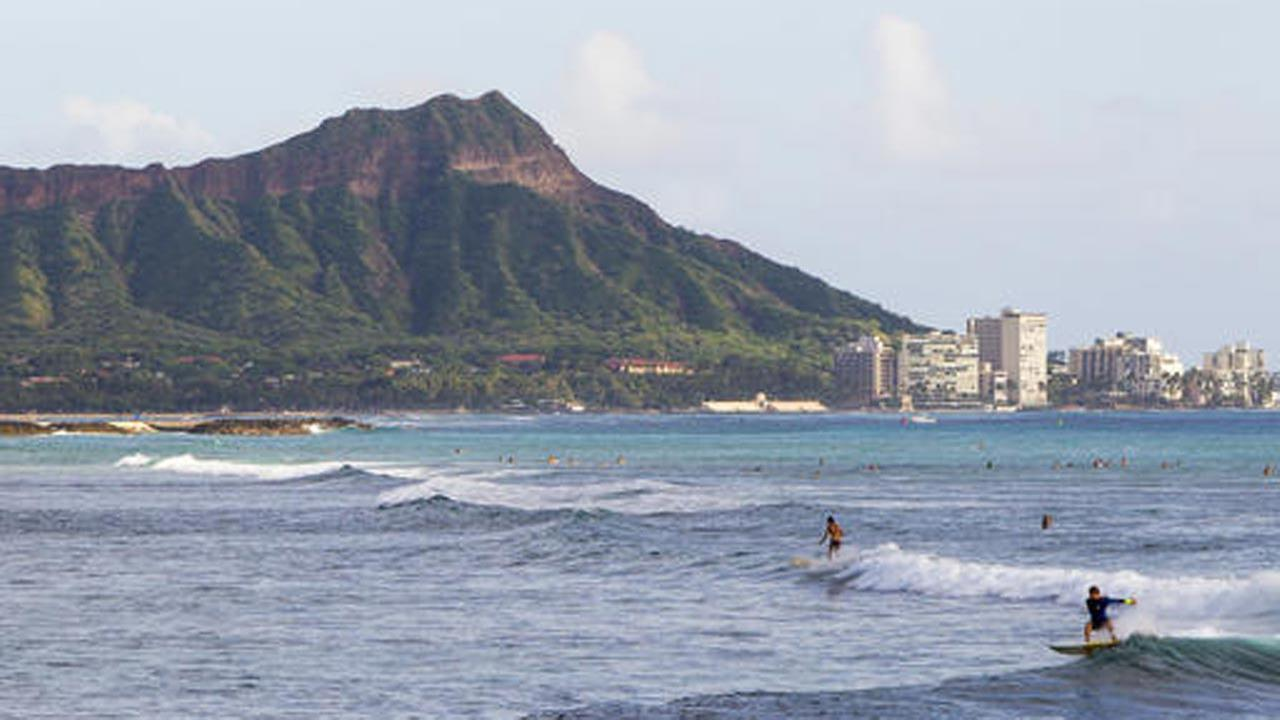 In this Nov. 4, 2014 file photo, surfers ride waves off Ala Moana Beach Park in Honolulu, with Diamond Head mountain in the background.