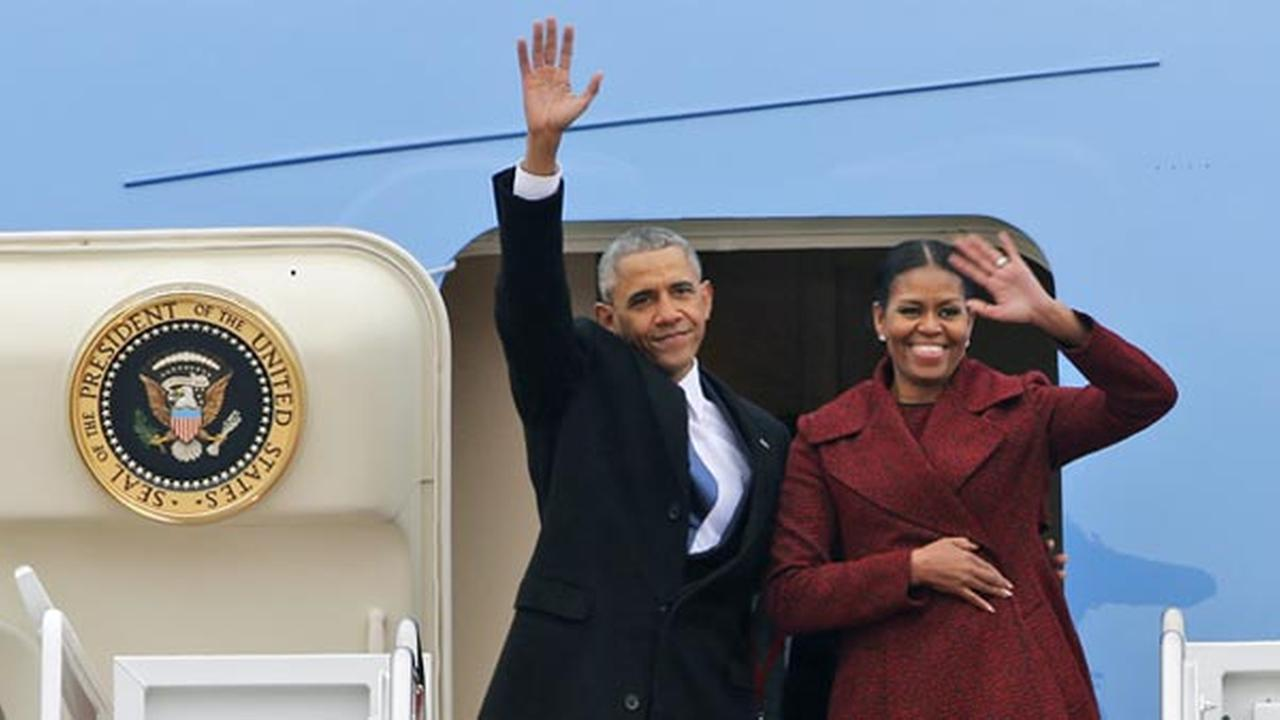 Former President Barack Obama and his wife Michelle wave to the crowd as they board an Air Force jet to depart Andrews Air Force base in Andrews Air Force Base, Md.