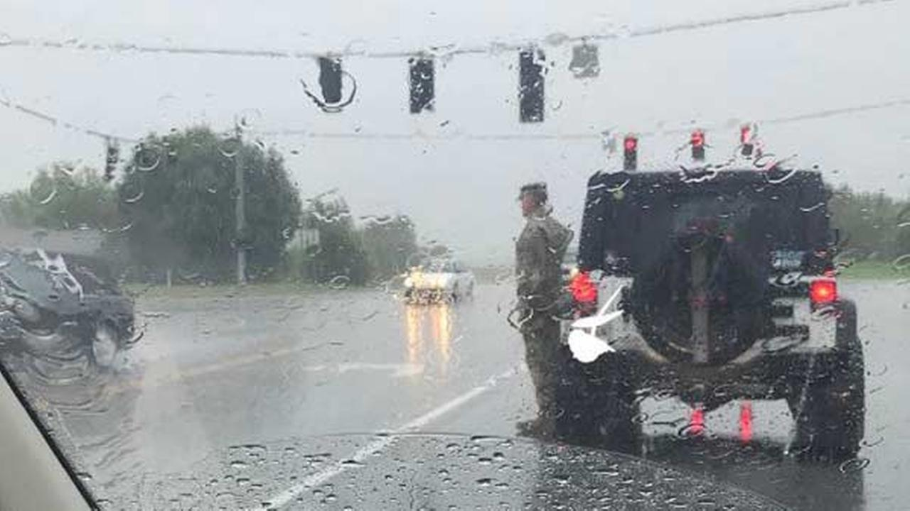 A photo of a soldier standing in the pouring rain to salute a passing funeral procession is going viral.