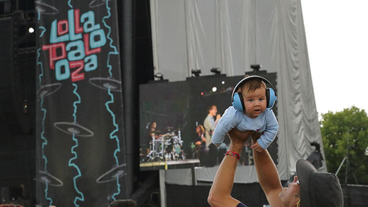 A man holds a baby wearing ear protection during a performance at the Lollapalooza in Chicagos Grant Park on Friday, Aug. 1, 2014.