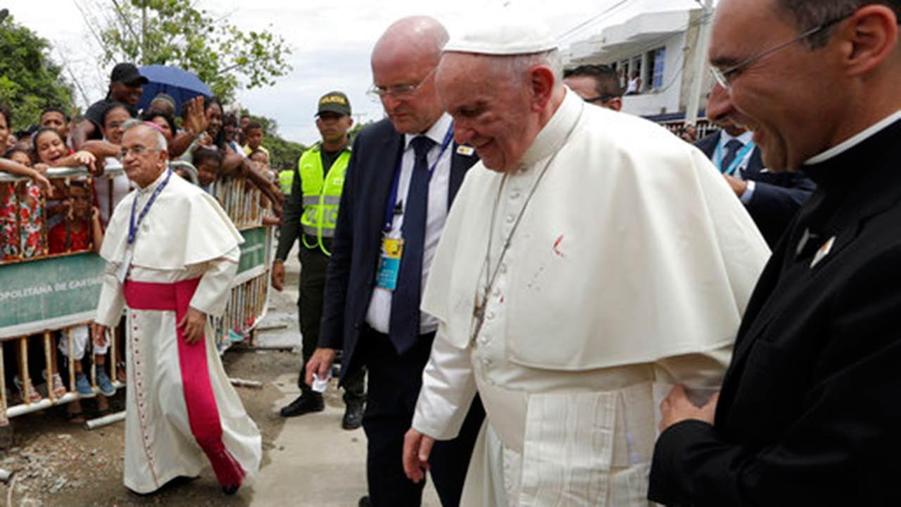 A small drop of blood stains Pope Francis white cassock as he is helped by a priest, after knocking his head on the popemobile in Cartagena, Colombia.
