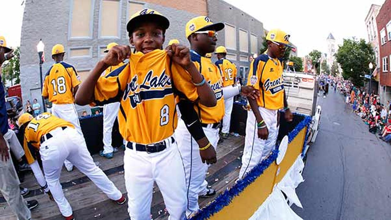 Members of the Jackie Robinson West Little League team from Chicago, Ill., ride in the Little League Grand Slam Parade as it makes its way through downtown Williamsport, Pa.
