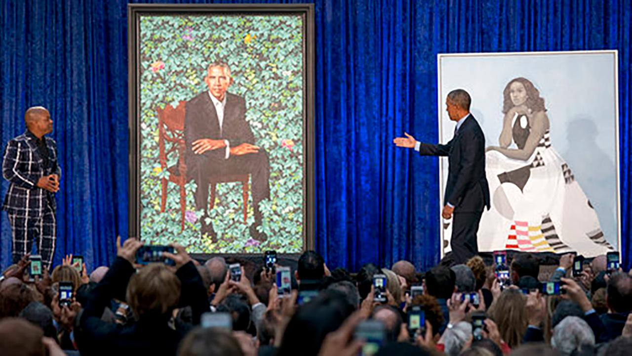 Former President Barack Obama, right, and Artist Kehinde Wiley, left, unveil the Obamas official portraits at the Smithsonians National Portrait Gallery.
