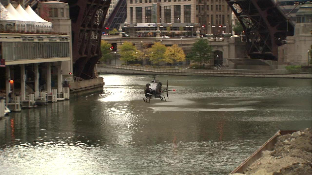 A helicopter flies low in the Chicago River during filming of the new movie Insurgent.
