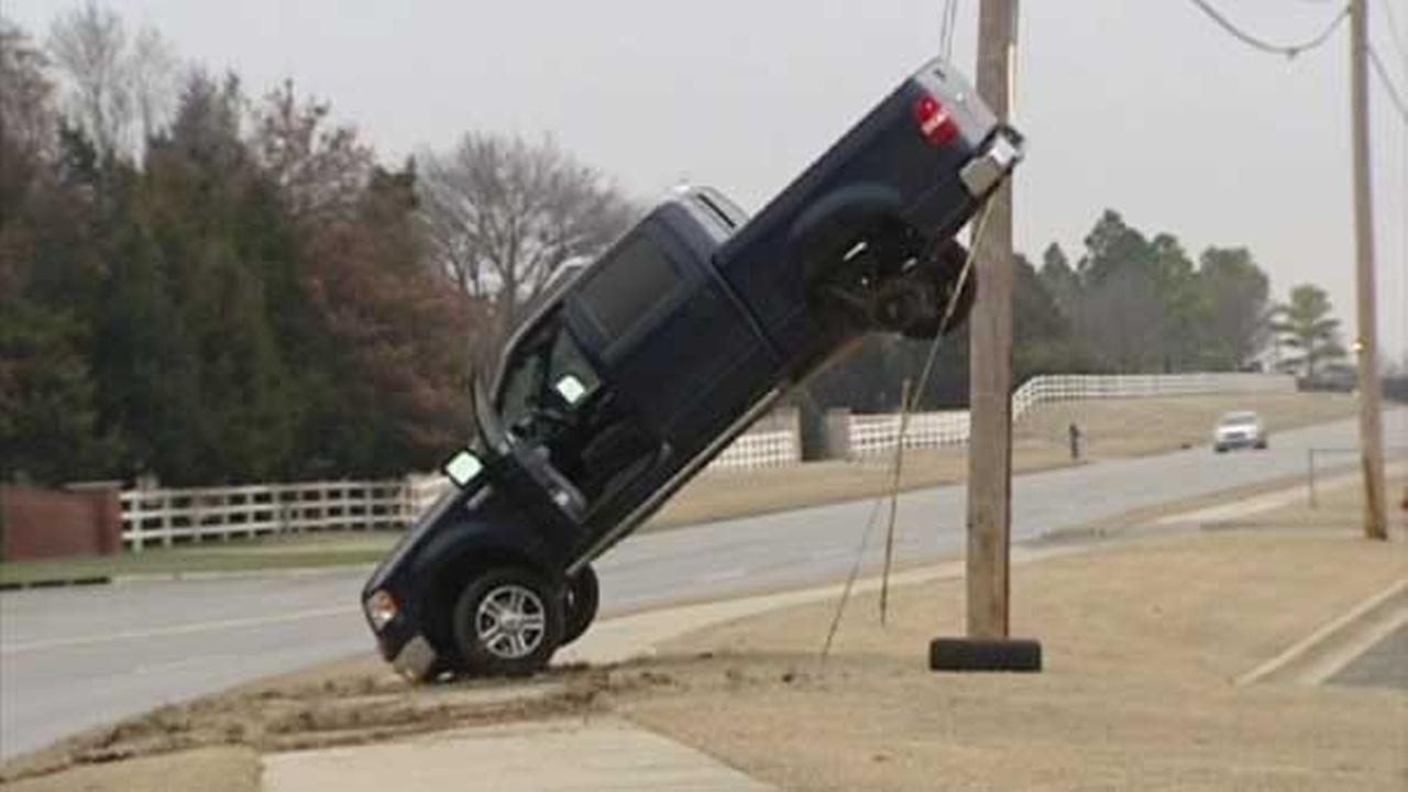 Truck dangles off power line after driver speeds on icy road in Oklahoma City