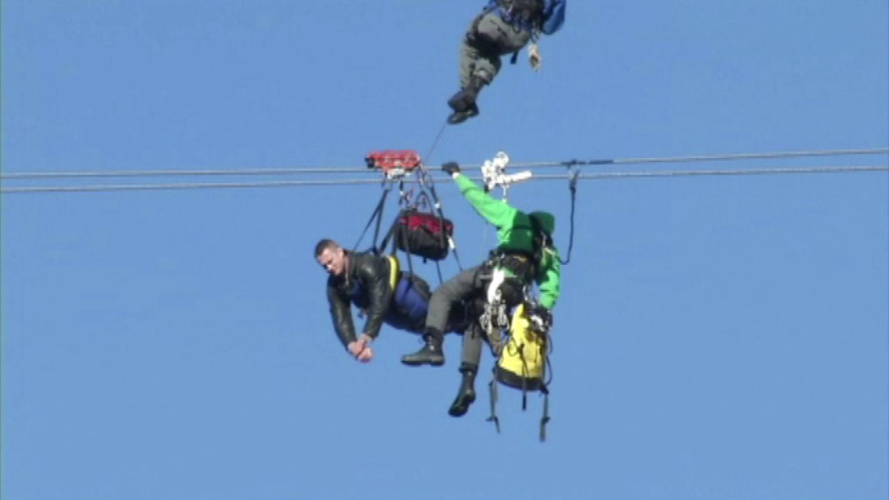 A Canadian tourist stuck dangling from a Las Vegas zip line about 80 feet above a street for nearly an hour is back on solid ground after being rescued by firefighters.