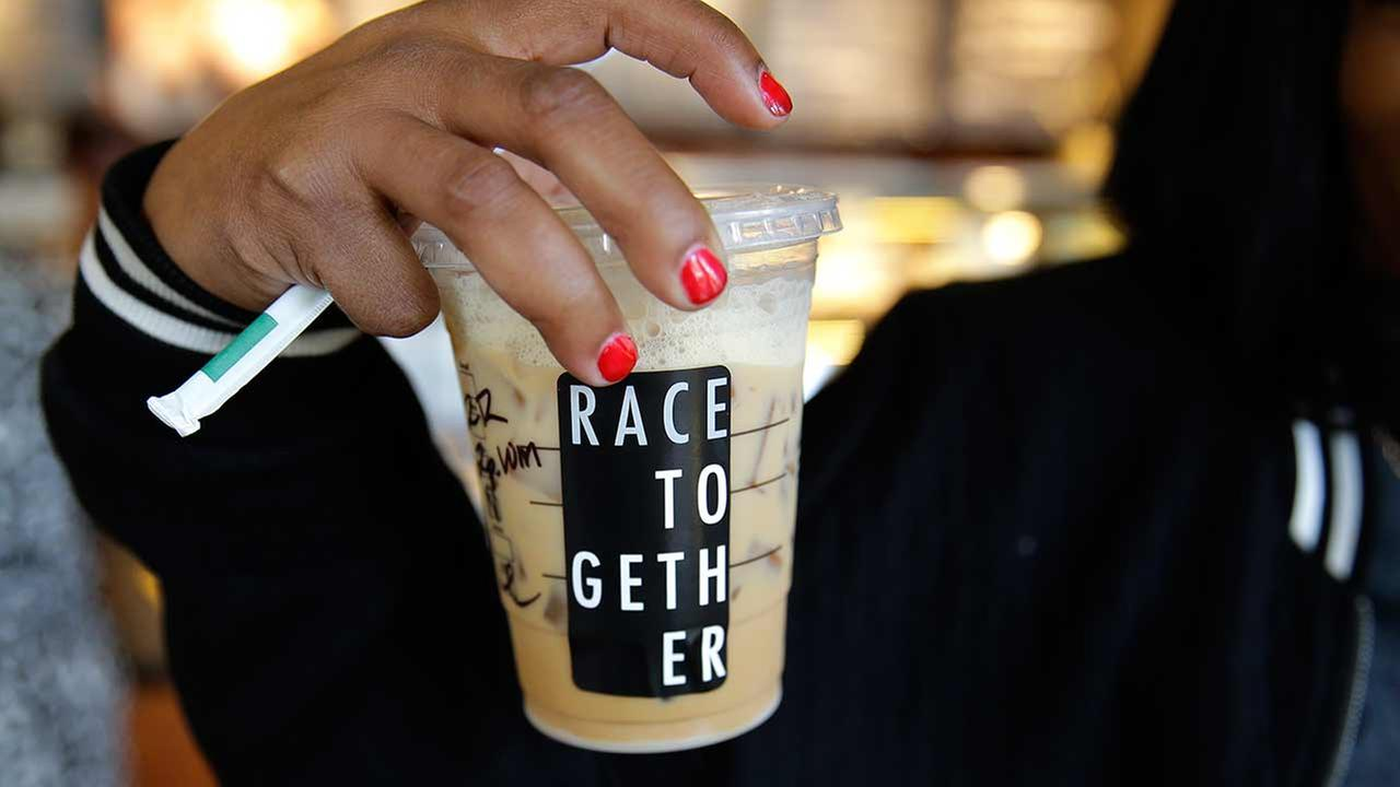 Larenda Myres holds an iced coffee drink with a Race Together sticker on it at a Starbucks store in Seattle, Wednesday, March 18, 2015.