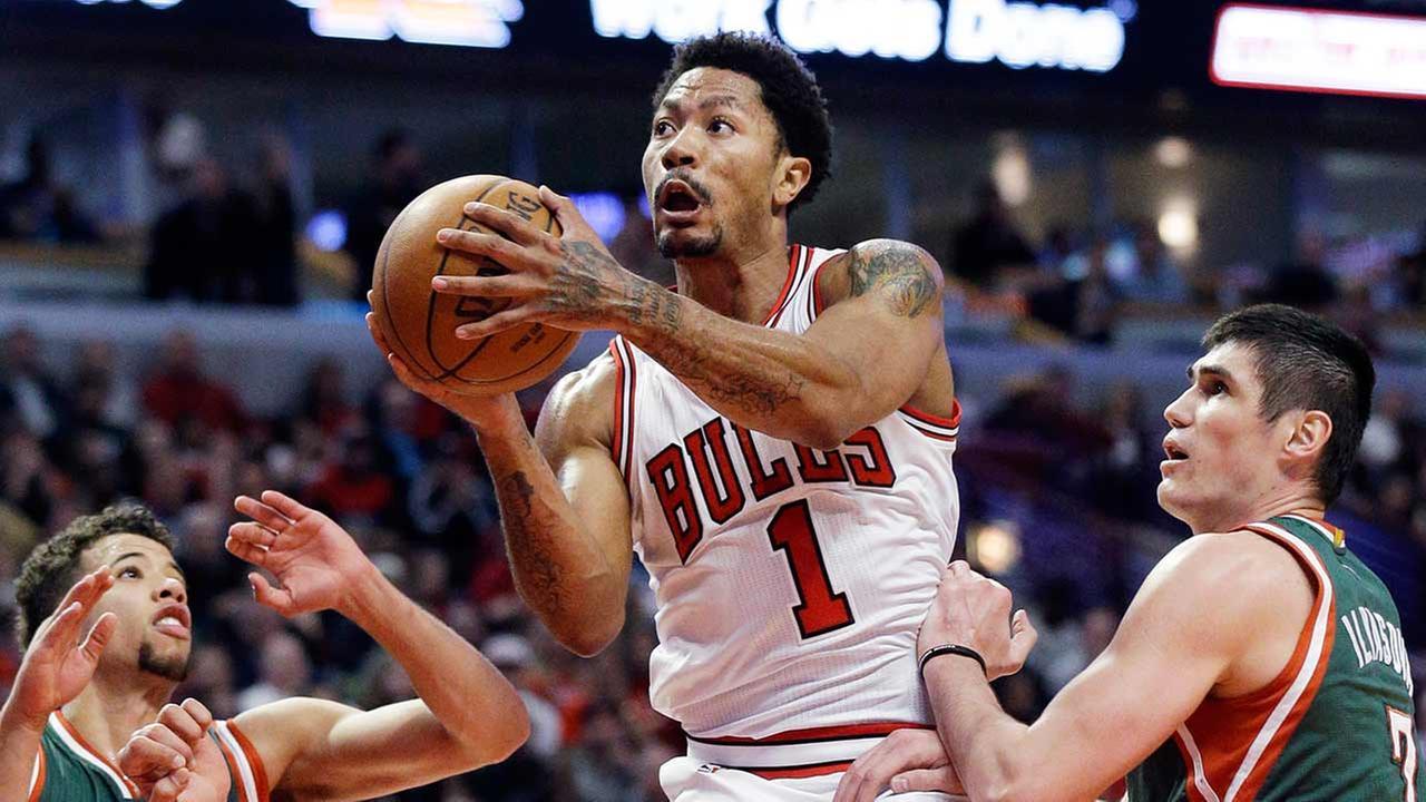 Chicago Bulls guard Derrick Rose, center, drives to the basket against Milwaukee Bucks forward Ersan Ilyasova.