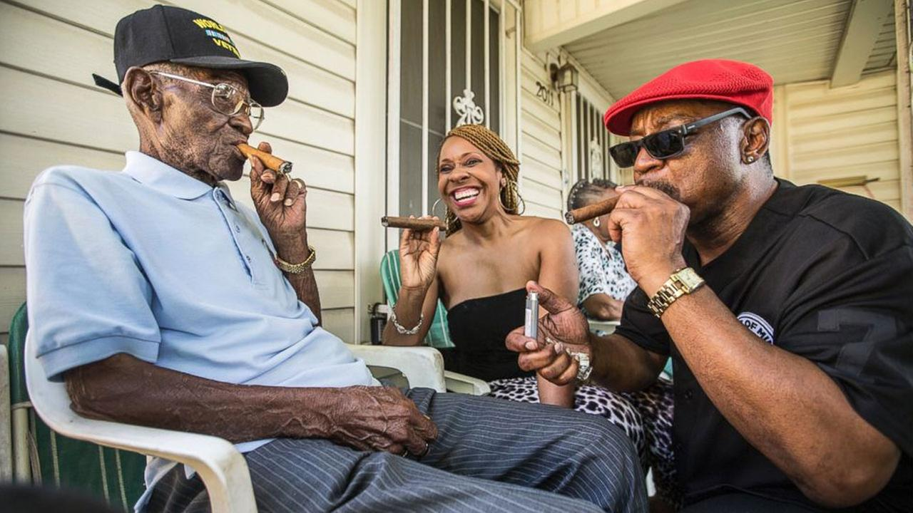 Richard Overton, left, smokes a cigar with neighborhood friends Donna Shorts, center, and Martin Wilford, right, on May 3, 2015 in Austin, Texas.